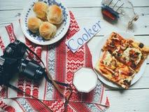 pizza casalinga, un bicchiere di latte, una vecchia macchina fotografica e focaccine al latte casalinghe su una tavola di legno Fotografia Stock