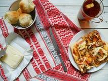 pizza casalinga, una tazza di tè con il limone, biscotti e burro su una tavola bianca Fotografia Stock