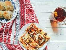 pizza casalinga, una tazza di tè con il limone e panini su una tavola bianca Immagini Stock Libere da Diritti