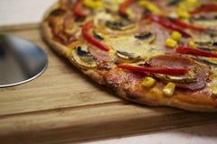 Pizza casalinga vicino ad un'affettatrice della pizza fotografia stock libera da diritti