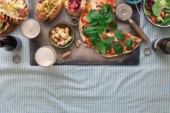 Pizza caseiro, cachorros quentes diferentes, cerveja e petisco para a cerveja Foto de Stock