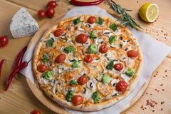 Pizza caseiro com em um fundo de madeira com frutas e legumes com especiarias fotos de stock