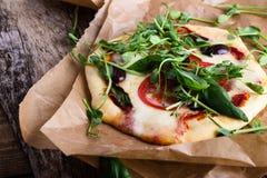 Pizza caseiro com os tomates e os brotos que cobrem na tabela rústica Fotografia de Stock Royalty Free