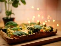 Pizza casera con albahaca en el fondo y las luces Fotos de archivo