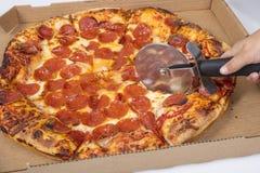 Pizza che è tagliata nelle fette immagini stock