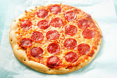 Pizza with cheese and pepperoni on blue surface royalty free stock photo