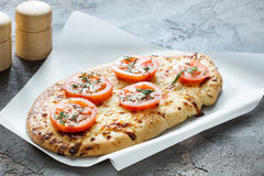 Pizza with cheese and tomatoes, herbs spices on a concrete backg. Georgian bread with cheese and tomatoes on a concrete background Royalty Free Stock Image