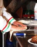 Pizza Chef. Hands of pizza chef preparing dough for pizza base Stock Photo