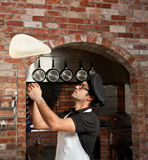 Pizza Chef playing with Pizza Dough. Pizza Chef makes the pizza dough spin in the air to make it thin and soft Royalty Free Stock Photo