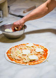 Pizza chef at work. Pizza chef spreading out and garnishing a delicious pizza Stock Photos