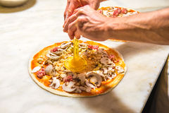Pizza chef at work. Pizza chef spreading out and garnishing a delicious pizza Stock Images
