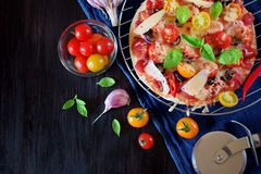 Pizza with cherry tomatoes, tomato sauce, cheese and basil leaves. Against the dark background. Mediterranean cuisine meal stock images