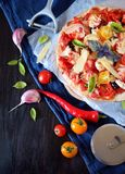 Pizza with cherry tomatoes, tomato sauce, cheese and basil leaves. Against the dark background. Mediterranean cuisine meal royalty free stock photos