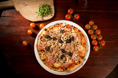Pizza with chicken, cheese and olives. Delicious pizza with fish, cheese and olives on wooden table; arugula and tomatoes on wooden paddle Stock Photos