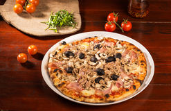 Pizza with chicken, cheese and olives. Delicious pizza with fish, cheese and olives on wooden table; arugula and tomatoes on wooden paddle royalty free stock photo