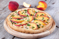 Pizza with chicken and peaches on a wooden board. Pizza with chicken and peaches Stock Photos