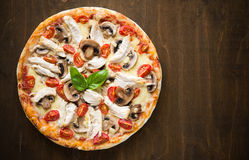 Pizza with chicken, tomato and mushrooms on dark wood background Royalty Free Stock Photo