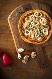 Pizza with chilly pepper mushroom with brown rustic table. Delicious pizza with red chilly pepper, unions and mushroom in brown background rustic table stock photography