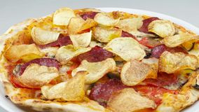 Pizza with chips and salami rotates stock video footage