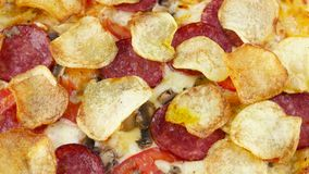 Pizza with chips and salami, top view stock video