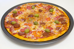Pizza with chorizo, salami, bacon, onions and olives Royalty Free Stock Images