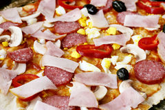 Pizza close-up. Pizza with salami, bacon and peppers on close-up Royalty Free Stock Photo