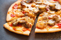 Pizza closeup. Closeup photography of tasty crusty Italian pizza with tomato sauce, mushrooms, chicken and melting cheese with one cut portion piece on cut table Stock Image