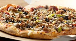 Pizza closeup with supreme toppings. Closeup photo of a pizza with supreme toppings in a cardboard box Royalty Free Stock Photos