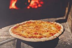 Pizza cocida fresca con queso cerca del horno Imagen de archivo
