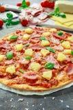 Pizza cocida fresca Hawaii con el jamón y la piña, albahaca, tomates en el papel apoyado Imágenes de archivo libres de regalías