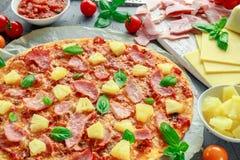 Pizza cocida fresca Hawaii con el jamón y la piña, albahaca, tomates en el papel apoyado Imagen de archivo