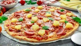 Pizza cocida fresca Hawaii con el jamón y la piña, albahaca, tomates en el papel apoyado Imagen de archivo libre de regalías