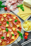 Pizza cocida fresca Hawaii con el jamón y la piña, albahaca, tomates en el papel apoyado Fotografía de archivo libre de regalías
