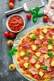 Pizza cocida fresca Hawaii con el jamón y la piña, albahaca, tomates en el papel apoyado Foto de archivo
