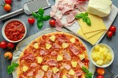 Pizza cocida fresca Hawaii con el jamón y la piña, albahaca, tomates en el papel apoyado Fotos de archivo