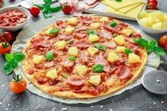 Pizza cocida fresca Hawaii con el jamón y la piña, albahaca, tomates en el papel apoyado Imagenes de archivo