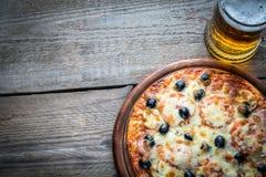 Pizza cocinada con un vidrio de cerveza Imagen de archivo libre de regalías