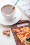 Pizza and coffee. Cup of coffee and pizza slice on the cutting board in bright light Royalty Free Stock Photo