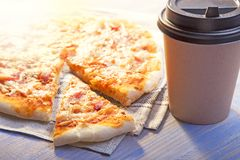 Pizza and Coffee on wooden table, cup of cappuccino. royalty free stock images