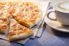 Pizza and Coffee on wooden table, cup of cappuccino. Royalty Free Stock Photo