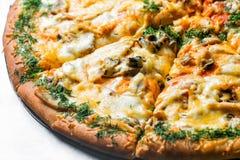 Pizza com cogumelos e vegetais, pelo corte às partes em uma tabela do metal foco seletivo no close-up de enchimento Foto de Stock