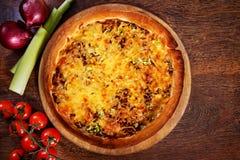 A pizza com enchimento, alho-porro e queijo da carne serviu na tabela de madeira Imagens de Stock Royalty Free