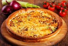 A pizza com enchimento, alho-porro e queijo da carne serviu na tabela de madeira Imagem de Stock