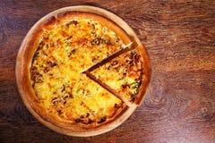 A pizza com enchimento, alho-porro e queijo da carne serviu na tabela de madeira Fotografia de Stock Royalty Free