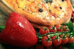 Pizza com fundo rústico dos vegetais e das ervas Fotos de Stock Royalty Free