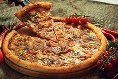 Pizza com fundo rústico dos vegetais e das ervas Fotografia de Stock