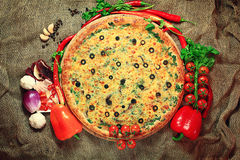 Pizza com fundo rústico dos vegetais e das ervas Imagens de Stock