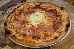 Pizza com molho de tomate, presunto, rolo da galinha, salsicha, ovo, queijo amarelo, azeite, orégano, placa do sésamo fotos de stock royalty free