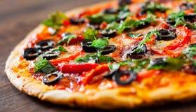Pizza com mozzarella, salame, pimenta, pepperoni, tomates, azeitonas, especiarias e manjericão fresca Pizza italiana Imagem de Stock Royalty Free