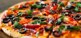 Pizza com mozzarella, salame, pimenta, pepperoni, tomates, azeitonas, especiarias e manjericão fresca Pizza italiana Fotografia de Stock